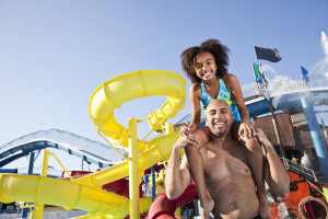 Girl, 8 years, and father, 40s, having fun standing in front of water slide