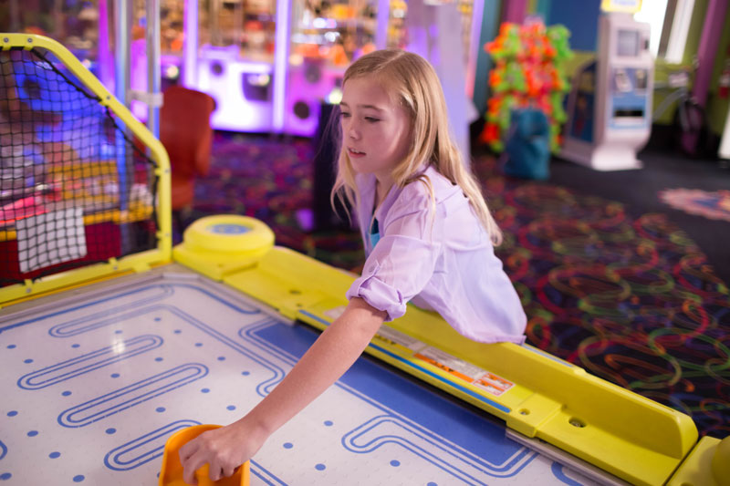 Young girl plays air hockey