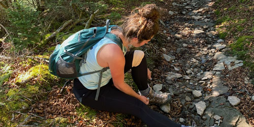 A hiker tightening her shoe laces