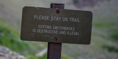A trail sign that reads: Please stay on trail. Cutting switchbacks is destructive and illegal.